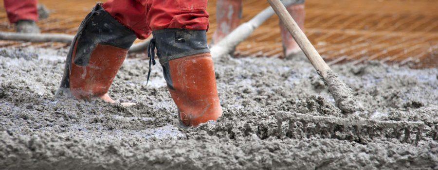 Group of construction workers spreading freshly poured concrete mix on the bridge - Concrete Paving Services in Houston TX - PavingRite Construction